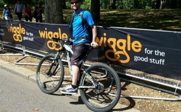 Andy con su bici en frente de una pancarta de Wiggle